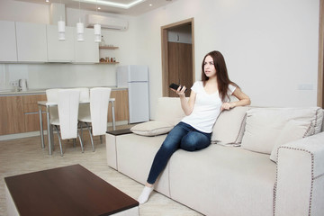 Beautiful young woman watching television