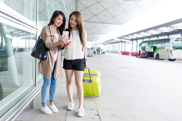 Girl friends using mobile phone in airport