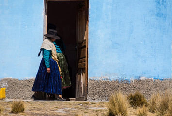 Young Ayamara women in the typical costume just outside her colored house. Aymaras are the native population of the Titicaca Lake area, in Bolivia, South America.