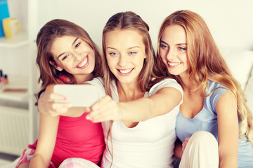 teen girls with smartphone taking selfie at home