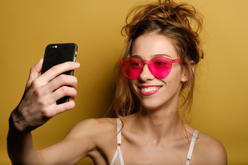 Funny portrait of a smiling young girl in pink glasses, which makes selfie on phone on yellow background