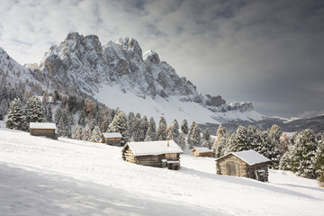 a winter view of the Puez Geisler Natural Park in Villnöss with some huts in foreground and the Geisler in the background, Bolzano province, South Tyrol, Trentino Alto Adige, Italy, Europe