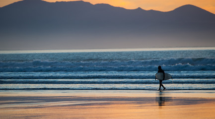 Surfer with surfboard walking out of the ocean at sunset