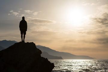 Hiking silhouette backpacker, man looking at ocean