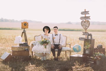 The smiling bride with bouquet and happy groom in vintage suit are sitting on the old-fashioned sofa surrounded by flowers, wooden plaques with signs, suitcases at the background of the spring field.