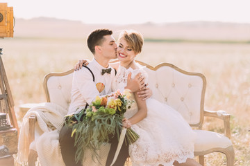 The romantic close-up portrait of the groom kissing the bride with the bouquet into the cheek in the sunny field. The bride is holding the wedding bouquet.