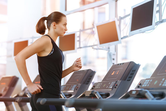 Young athletic woman running on a treadmill at the gym