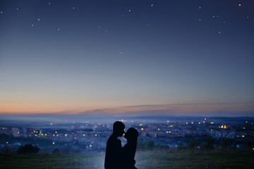 Silhouette of a couple in love against the background of a night city, stars and horizon. Concept is a date on the roof, the first love