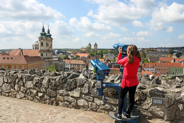 little girl looking through sightseeing binoculars on Eger cityscape