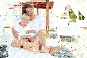 Luxury resort happy family relaxing . Mother and daughter lying down on deckchair of beach resort . Summer vacation idea.