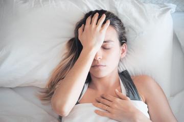 Donna con mal di testa a letto, emicrania e sinusite