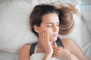 Donna con dolore ai denti a letto