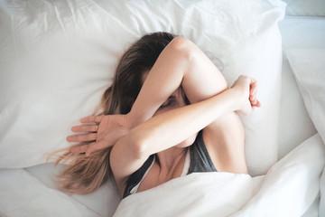 Donna stanca a letto al mattino