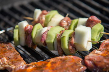 close on raw meat with fruits on the grill