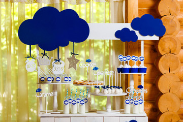 Candy bar on baby's christening party with a lot of different candies and beverages. Decorated in blue colors, clouds theme, indoor