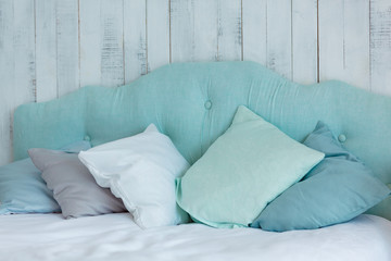 Lots of pillows in blue tones, laid out on a bed, on a wooden ba