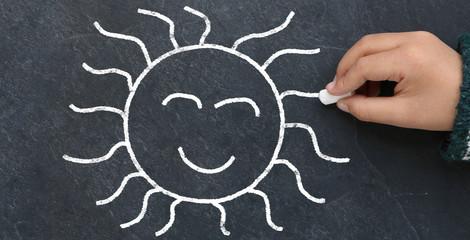 Enfant dessinant un soleil sur une ardoise
