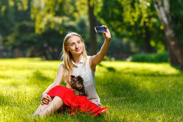 Young beautiful woman taking selfie with her dog - small Yorkshire terrier. Summer, park