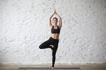 Mid aged yogi smiling attractive woman practicing yoga concept, standing in Vrksasana exercise, Tree pose, working out, wearing sportswear, black top and pants, full length, white loft background