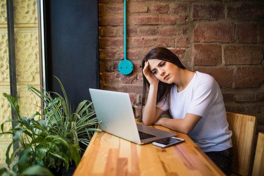 Worried woman holding computer, laptop tablet screen looking surprised in coffee shop