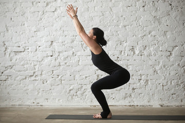 Young yogi attractive woman practicing yoga concept, doing advanced Chair exercise, Utkatasana pose, working out, wearing sportswear, black tank top and pants, full length, white loft background