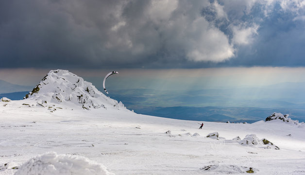 Snowkite on a mountain top under storm clouds and the rays of the setting sun