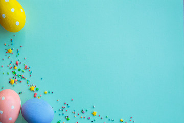 Easter background. Multicolored decorated easter eggs, multi-colored powder on a turquoise background. Free space