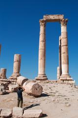 Giordania, 01/10/2013: un uomo di spalle fotografa le rovine del Tempio di Ercole, la struttura romana più significativa nella Cittadella di Amman, sito archeologico e nucleo originario della città
