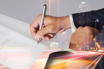 Double exposure of businessman hand holding a pen signing to the document, light trails on the street and urban in the night as business approval concept.