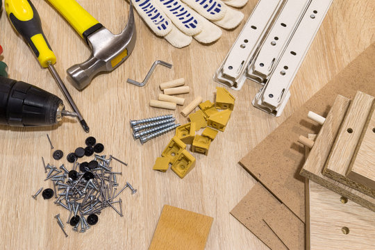 Furniture assembly components and tools arranged in a still life on a table.