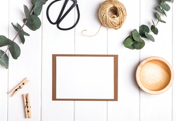 Blank paper with eucalyptus branches and little wooden objects
