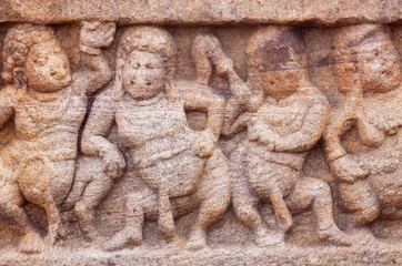 Dancing overweight people on stone relief of 7th century temple in Badami town, India. Famous for rock cut architecture of Karnataka