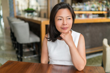 Elegant Asian middle-aged businesswoman pensive portrait. Beautiful mature Chinese business woman relaxing in restaurant bar urban stylish living in Shanghai, China. Mindfulness concept.