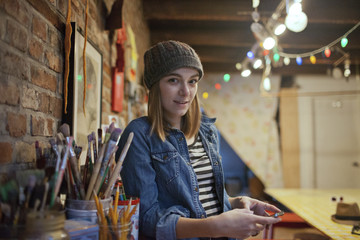 Portrait of young woman using smartphone while standing in studio