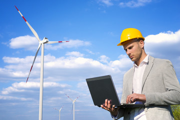 Renewable energy sources. Man working on his laptop. Wind generators in the background.