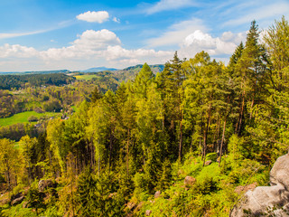 Summer time landscape with green forest, sandstone rocks and blue sky with white clouds, Bohemian Paradise, aka Cesky Raj, Czech Republic, Europe.