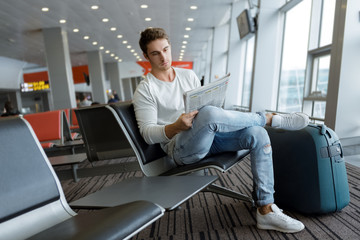 Handsome young man waiting for his departure at the airport lounge
