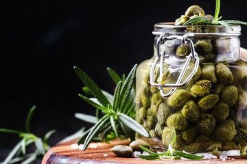 Capers with vinegar, salt and rosemary on a dark background, selective focus