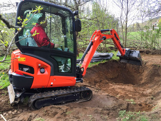 Small excavator with man inside, at work making garden pond