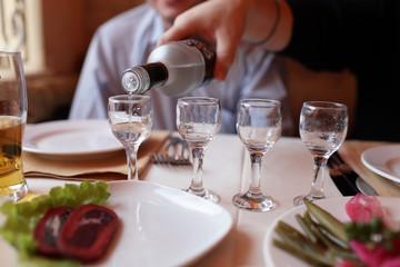 Filling glasses of vodka