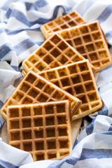Fresh homemade belgian waffles on striped napkin. Selective focus