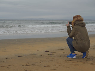 A woman taking picture on her phone.