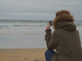 A modern woman using her smart phone to take pictures of ocean's wave.