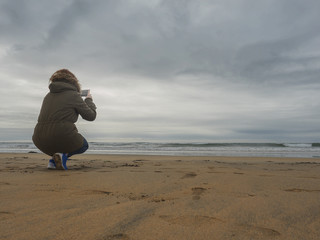 Woman taking photograph of waves and dramatic sky on her smartphone.