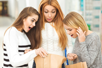 Beautiful girlfriends looking shocked while shopping at the mall