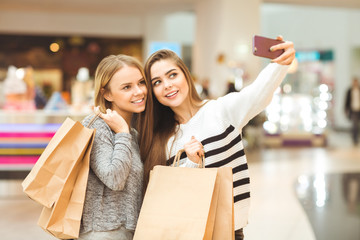 Cheerful young girlfriends taking a selfie while shopping at the local mall
