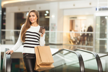 Attractive young woman enjoying her coffee at the shopping mall