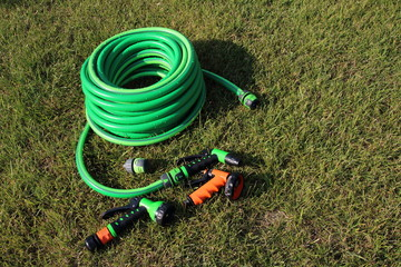 Garden hose bundle, connector and various adjustable showers (spray) on the mown lawn in the summer garden
