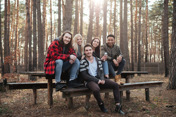 Happy group of friends sitting outdoors in the forest.