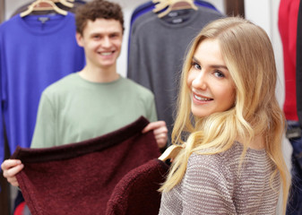 Happy young couple choosing clothes in modern shop
